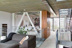 Graues Sofa vor Treppengeländer aus Edelstahl, im Hintergrund Loungebereich in offenem Wohnraum zeitgenössischer Architektur