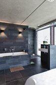 Schlafzimmer mit offenem Badbereich in Designerstil, Schieferfliesen an Wand und Boden