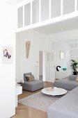 Moderne, graue Sofaelemente und elegant puristischer Coffeetable in offenem Wohnraum