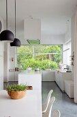 Weisse, offene Küche mit grossem Fensterelement zum Garten, vorne Esstisch mit Schalenstühlen