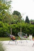 Retro Schalenstühle mit Schnurbespannung und Beistelltisch auf Terrasseplatz im Garten