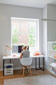 Moderner, heller Home-Office vor Fenster, Frau auf Schalenstuhl