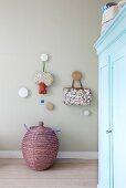 Runde Wandhaken über Deckelkorb, im Vordergrund hellblauer Vintage Kleiderschrank