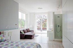 Blick vom offenen Schlafraum auf Sofa in lichtdurchflutetem Bad Ensuite mit Dusche