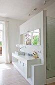 Kubisches Waschtischregal und Wandspiegel vor Duschkabine im offenen Bad Ensuite