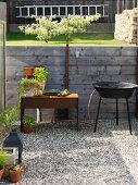 Potted herbs and harvested vegetables on rusty metal side table next to barbecue on gravel area in garden