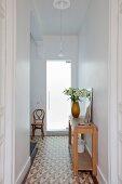 Flur mit Fliesenboden und Wandtisch, im Hintergrund Thonetstuhl neben Glastür