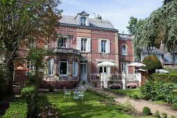 Sunny garden of traditional 19th-century, brick villa