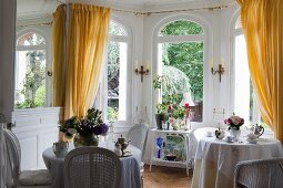 Set bistro tables in front of arched windows with yellow curtains in grand window bay