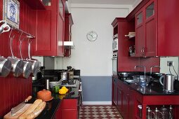 Galley kitchen with red-painted, country-house-style cabinets and chequered floor