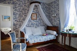 Antique sleigh bed with canopy against white and blue toile de jouy wallpaper