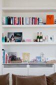 Modernes Schrankelement in weißer maßgefertigter Regalwand für Bücher, Fotos und Erinnerungsstücke