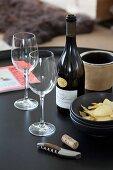Edle Weinflasche mit zwei Weingläsern, Chipsschale und Korkenzieher auf schwarzem Tabletttisch