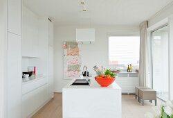 Weiße Corian-Designerküche mit Küchentheke und orangefarbener Obstschale