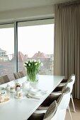 Weißer Esstisch mit Frühstücksgedeck, weißem Tulpenstrauß und gepolsterten Designerstühlen vor Fensterfront