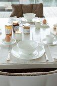 Zwei weiße Frühstücksgedecke mit Silberbesteck, Frühstücksei und Marmeladengläser