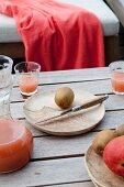 Kiwi auf Holzteller mit Saftgläsern und Glaskaraffe auf Holztisch