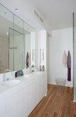 Elegantes weißes Bad mit maßgeferigtem Doppelwaschtisch, Wandspiegel und Teakholzparkett
