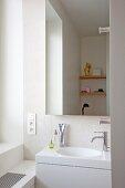 Elegantes weißes Corian-Waschbecken in Nische mit Wandspiegel