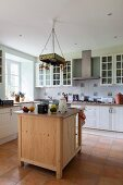 Free-standing wooden counter in country-house kitchen with terracotta-tiled floor
