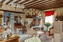 Eclectic furnishing and fireplace in renovated farmhouse