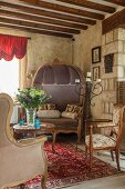 Antique chairs and sofa in renovated country house with rustic wood-beamed ceiling