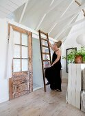 Woman wearing black climbing rustic wooden ladder in country-style summer house with white-painted wood-clad interior