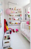 Child's bedroom with white cot, wall-mounted shelves and toys in wooden crates on castors