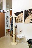 Retro Standgarderobe neben Waschbecken, oberhalb Zeichnungen an Wand