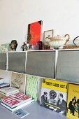 Auf gehängten Kästen mit Metallklappe Sammlerstücke, darunter Bücher auf Ablage