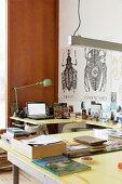 Hellgelbe Tischplatten in U-Form, Retro Tischleuchte, im Hintergrund grafische Zeichnungen von Insekten im Arbeitszimmer