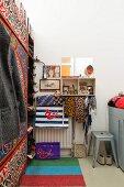 Schmaler Schlafraum mit gestreiftem Teppichläufer, Retro Metallhocker und Kleiderschrank mit folkloristischer Bemalung