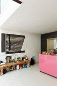 Holzbank mit Flaschen, oberhalb Zeichnung an Wand, seitlich Ausschnitt der Kücheninsel mit pinkfarbener Front
