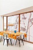 Retro Stühle um Tisch mit orangefarbener Tischdecke vor Fenster mit Rollos
