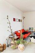 Bodenvase mit Blumenzweigen, rotes Designersofa und Hocker mit Kuhfellbezug, in minimalistischem Wohnraum