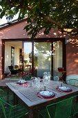 Gedeckter Gartentisch unter Laubbaum mit Blick auf geöffnete Giebelfassade