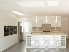 Shell-seat bar stools at sink unit in white designer kitchen