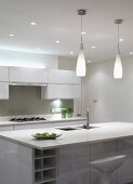 Bottle-shaped pendant lamps above sink unit with breakfast bar in designer kitchen