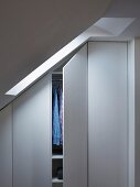 Wardrobe without handles and with one half-open door fitted below sloping ceiling; light falling through skylight