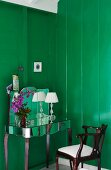Dressing table with mirrored surfaces and antique chair against wooden walls painted a rich green