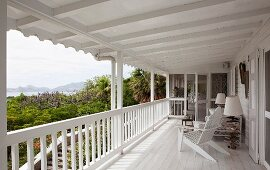Long, white wooden veranda with view of coast and maritime-style furnishings