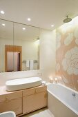 Floral tiled mosaic above bathtub and washstand with oval sink and tassels on drawers