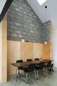 Black wooden shell chairs at retro-style chair against concrete block wall with wooden panelling