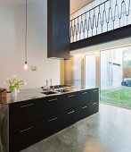 Designer kitchen counter with black drawers and stainless steel handles below extractor hood in minimalist interior; view through floor-to-ceiling window in background