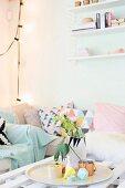 Kissen mit grafischen Mustern auf Polstersofa im Zimmerecke, im Vordergrund Tablett mit Vase und Papierdeko auf Couchtisch