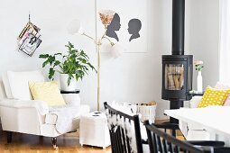 Dining area with black chairs, log burner and antique armchair with pale cover next to retro standard lamp