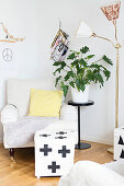 Pouffe with graphic pattern on pale cover in front of armchair, house plant on plant stand and retro standard lamp