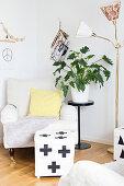 Hell bezogener Hocker mit grafischem Muster vor Sessel, seitlich Zimmerpflanze auf Blumenständer, neben Retro Stehleuchte