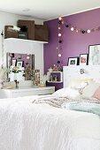 Bett mit weisser Tagesdecke in modernem Schlafzimmer, Lampiongirlande an violett getönter Wand aufgehängt