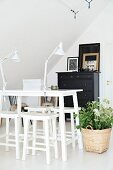 Table and stools painted white and plant in basket on floor of attic room